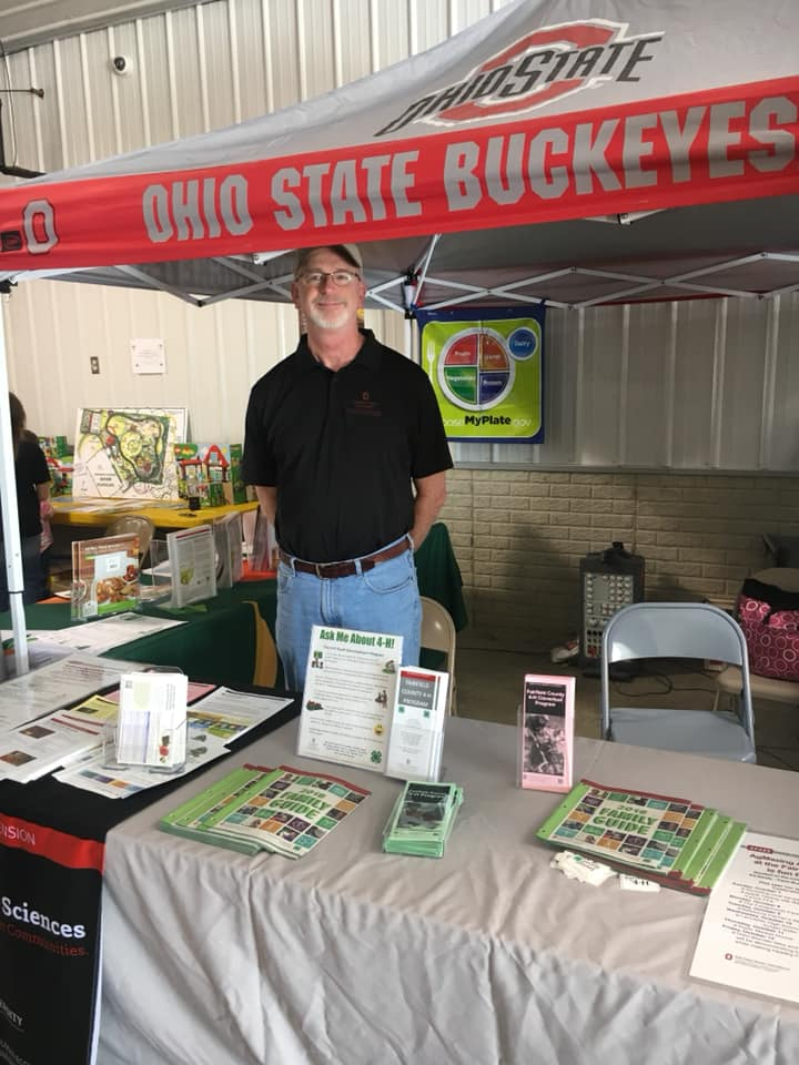 Jerry Iles standing in OSU Extension fair display booth