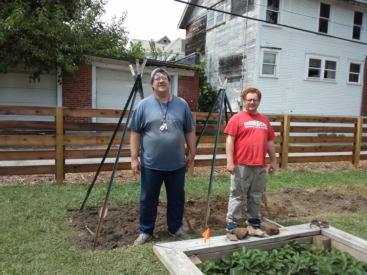 2 Adult Green Machine Gardeners next to a garden bed