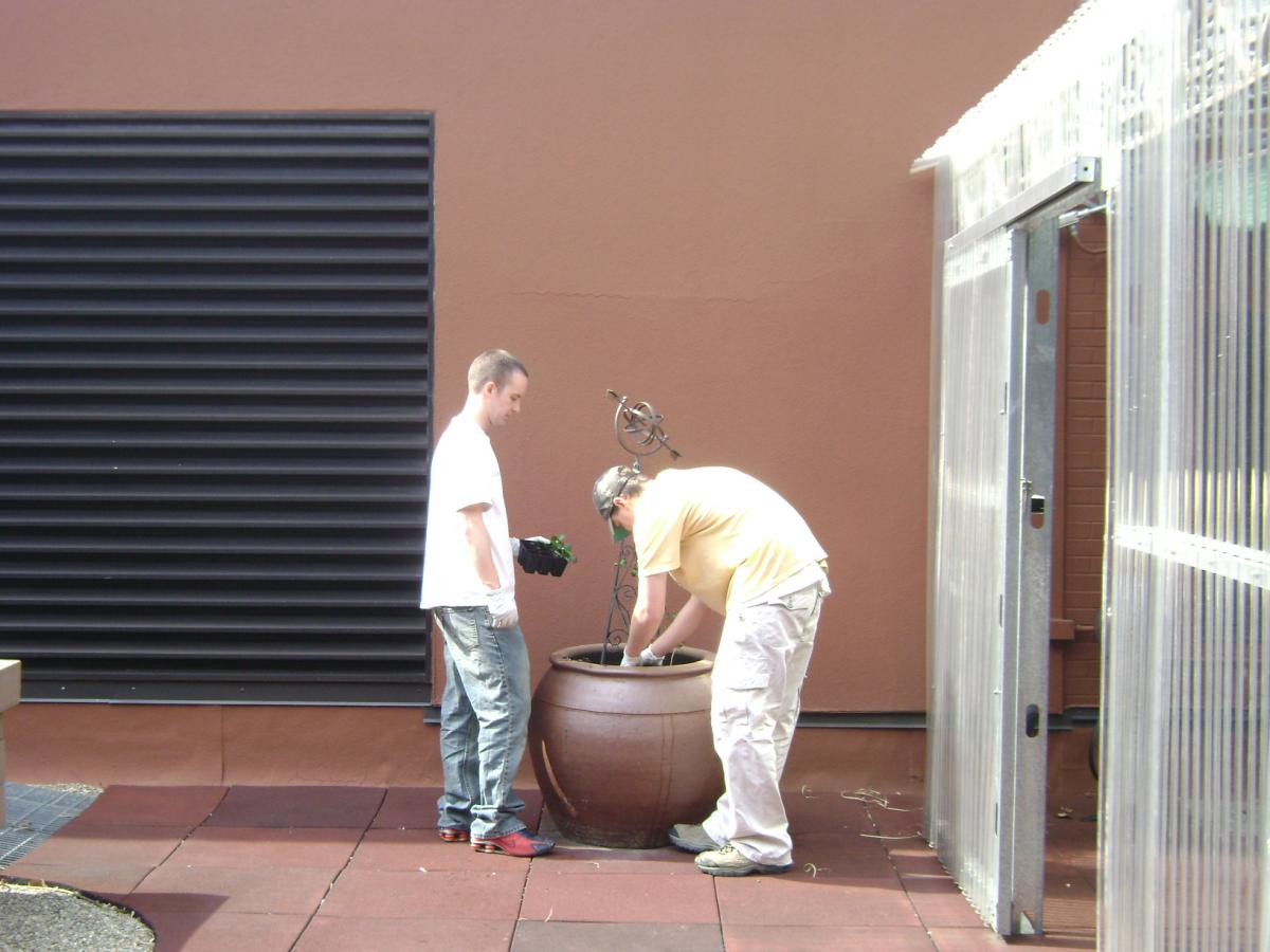 two master gardener volunteers working with plants in a clay pot at the Tranquility Gardens at FMC